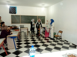 A presentation of different types of clothing that are worn by people in the south. At right is a beautiful kaftan. The girl in the center is wearing an Amazigh outfit, such as would be worn for a wedding, with gorgeous silver and coral jewelry.